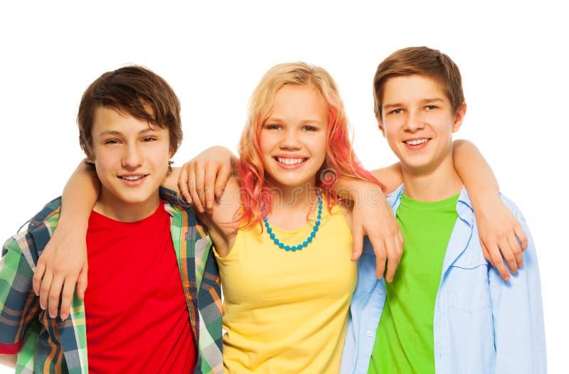 Gruppe von drei glücklichen Teenagerjungen und Mädchen umarmen lizenzfreie stockfotografie