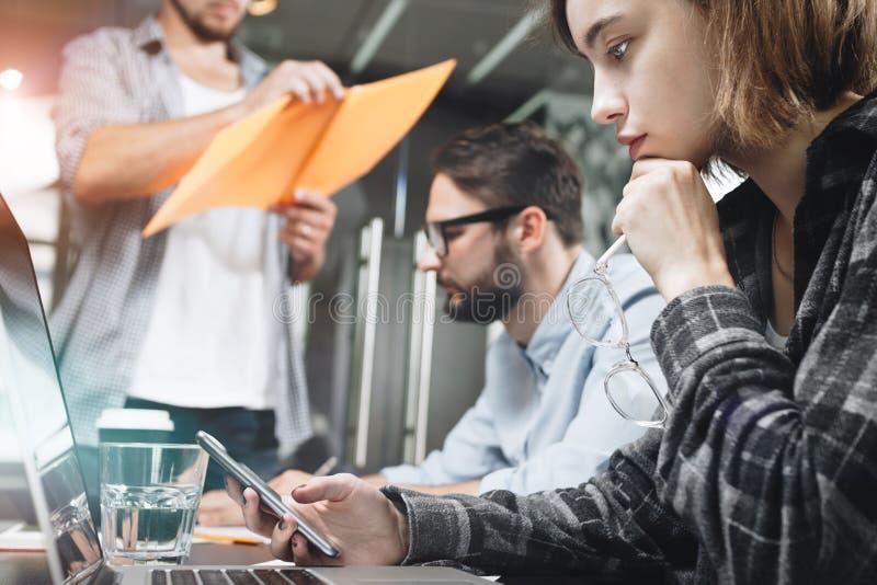 Gruppe von drei Mitarbeitern, die im modernen Dachbodenraum zusammenarbeiten W lizenzfreies stockbild