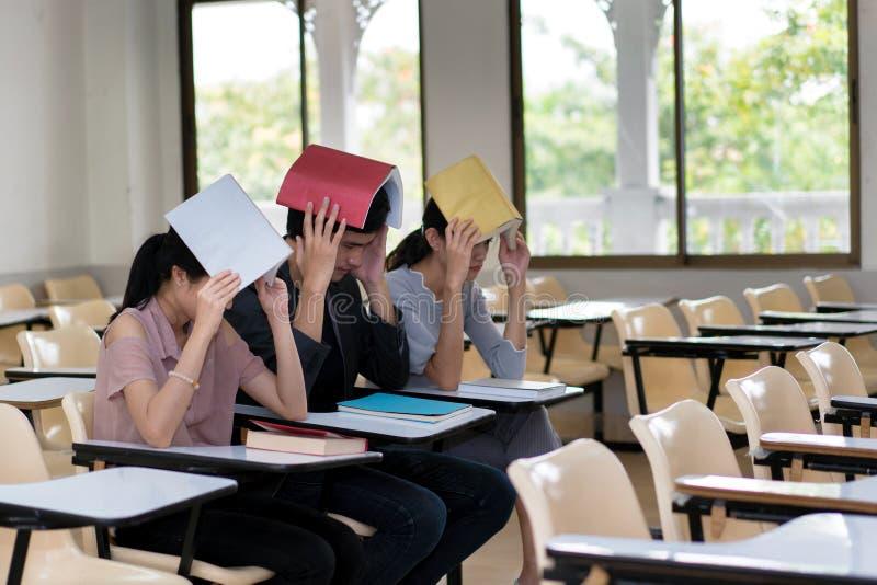 Gruppe von drei Studenten, die eine Abdeckung verwenden, buchen auf dem Kopf im Cl stockfoto