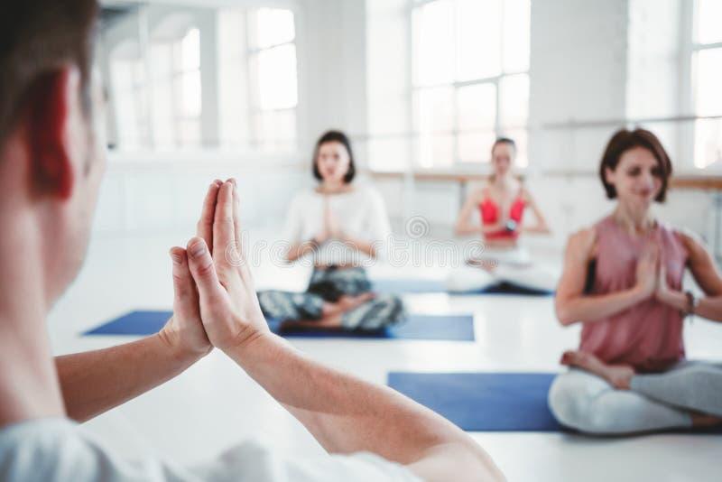 Gruppe von erwachsenen Frauen und von Mann, die zusammen Yogaübungen in der Eignungsklasse tut Aktive Leute üben Yogahaltungen au lizenzfreie stockfotografie