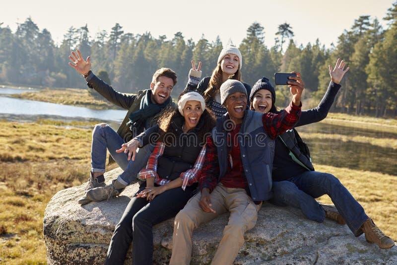 Gruppe von fünf Freunden nehmen ein selfie nahe in der Landschaft lizenzfreies stockbild