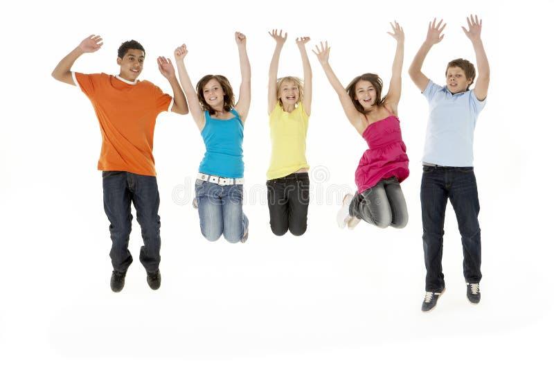 Gruppe von fünf jungen Kindern, die in Studio springen stockbild