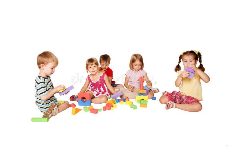 Gruppe von fünf kleinen spielenden und errichtenden Kindern stockfotografie