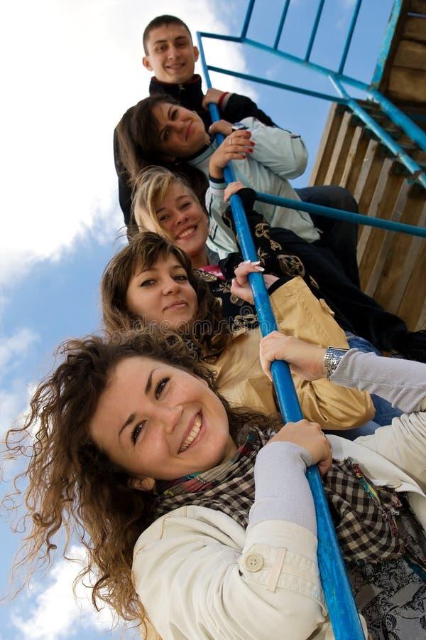 Gruppe von fünf lächelnden jungen Leuten auf den Treppen stockfotos