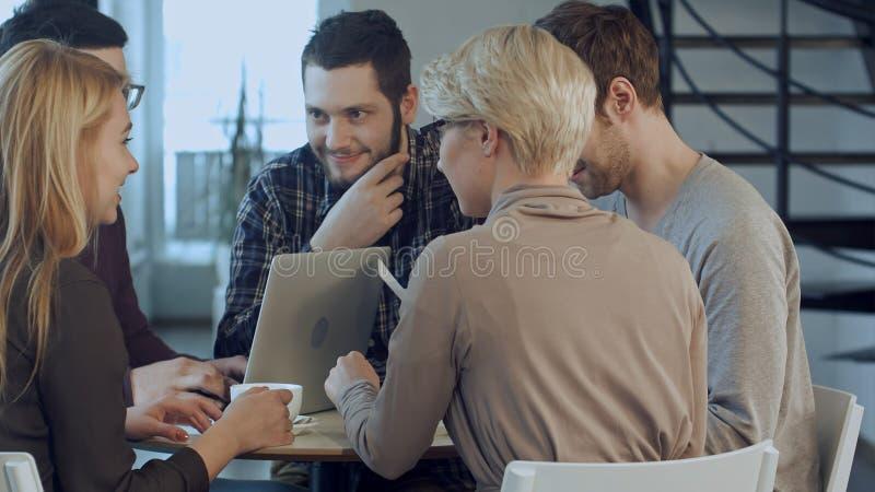 Gruppe von fünf Leuten, die etwas mit Lächeln beim Sitzen am Bürotisch besprechen stockbild