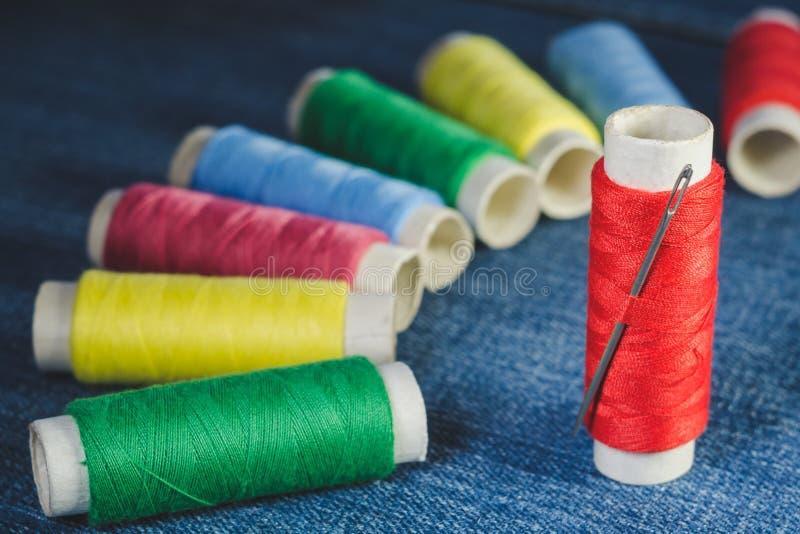 Gruppe von farbigen Fadenspulen und -Nähnadel auf Denim stockfotografie