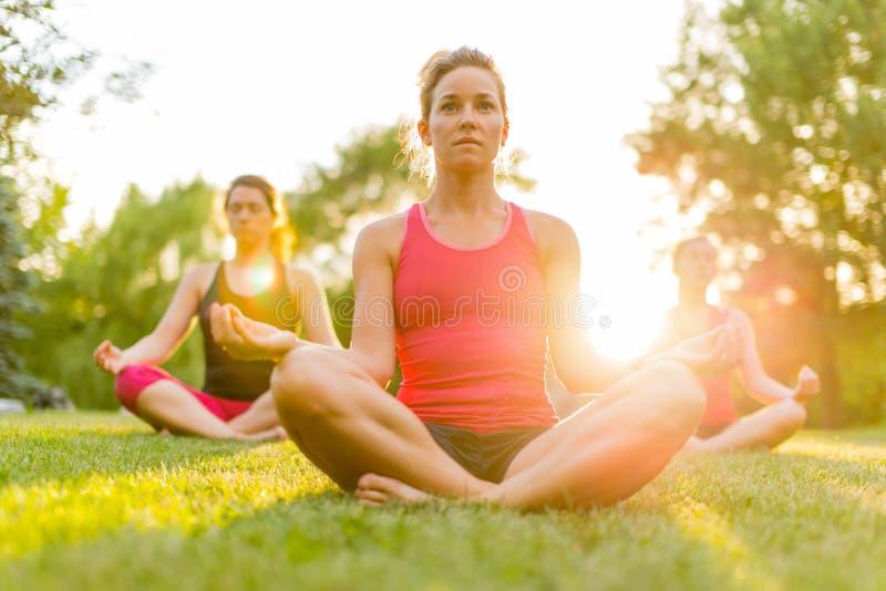 Gruppe von 3 Frauen, die Yoga in der Natur tun lizenzfreie stockfotografie
