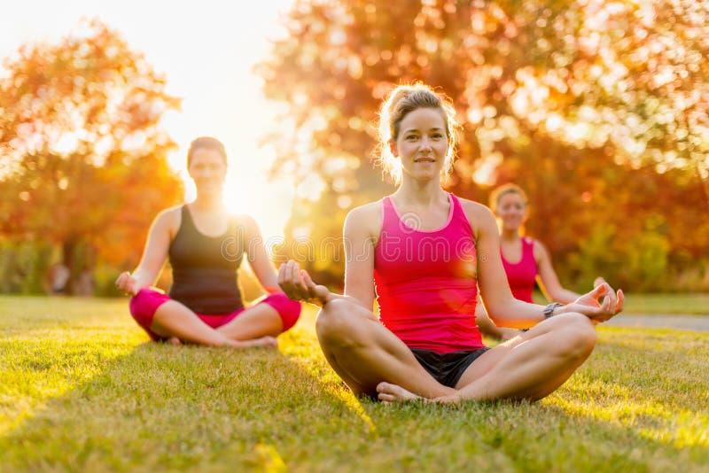 Gruppe von 3 Frauen, die Yoga in der Natur tun stockfotos