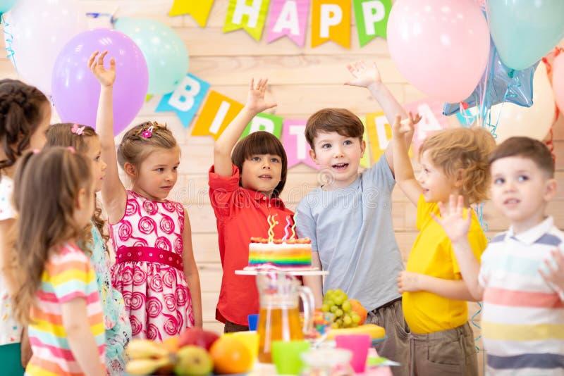 Gruppe von 3-5 gealterten Kindern, die fröhlich Geburtstagsfeier feiern stockbild