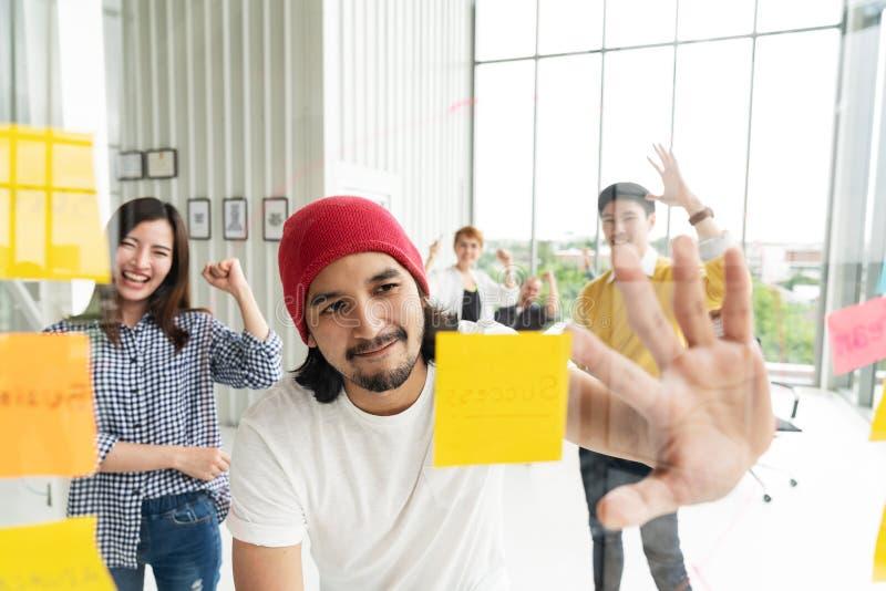 Gruppe von jungem erfolgreichem kreativem multiethnischem Teamzusammen lächeln und Geistesblitz im modernen Büro Glückliches Scha stockbild