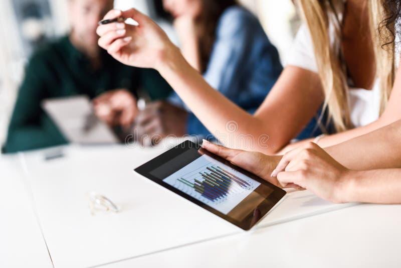 Gruppe von jungen Männern und von Frau, die mit Tablet-Computer coworking ist lizenzfreie stockfotos