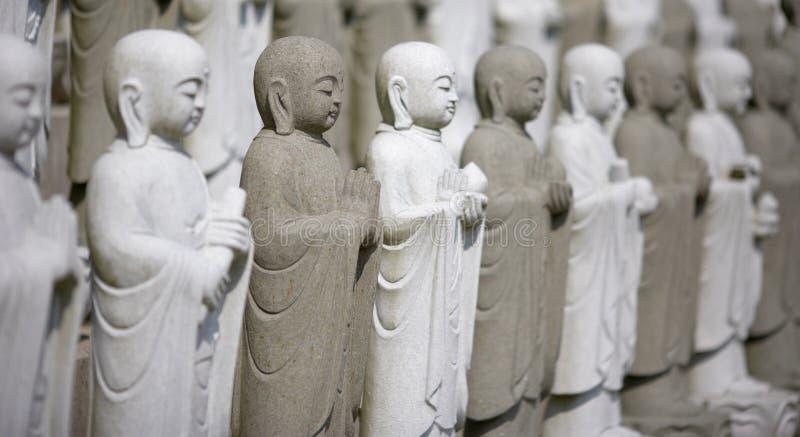 Gruppe von meditierendem Buddhas stockfotos