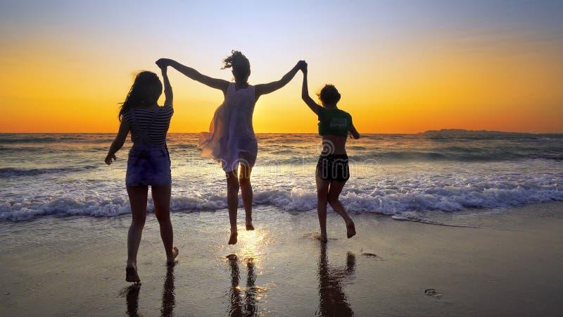 Gruppe von Personen auf dem Strand im Sonnenuntergang, der für die Hände haben Spaß hält lizenzfreies stockfoto