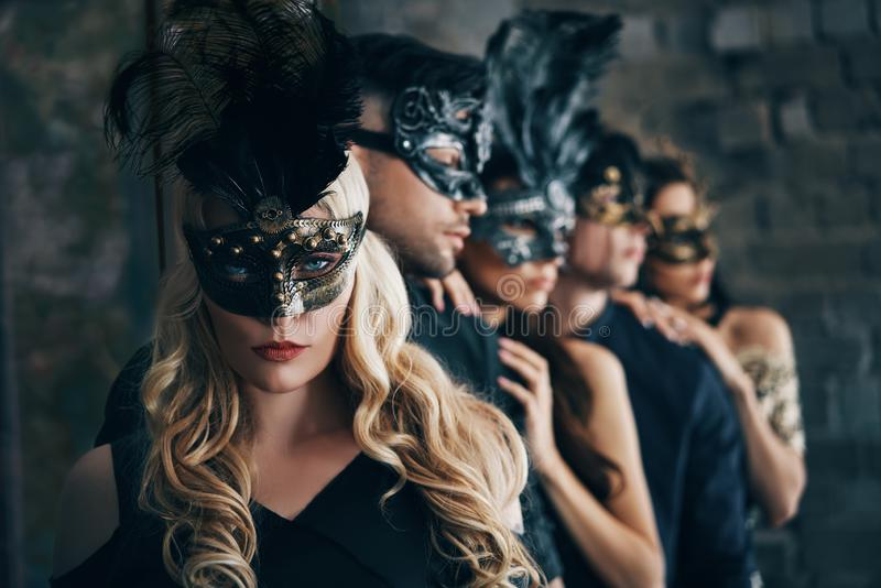 Gruppe von Personen in der Maskeradekarnevalsmaske, die im Studio aufwirft stockbild