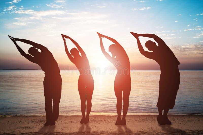 Gruppe von Personen, die ?bung auf Strand ausdehnend tut lizenzfreie stockfotografie