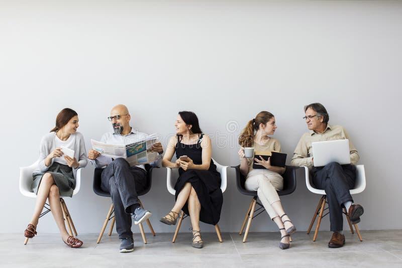 Gruppe von Personen, die auf Stühlen sitzt stockfotografie
