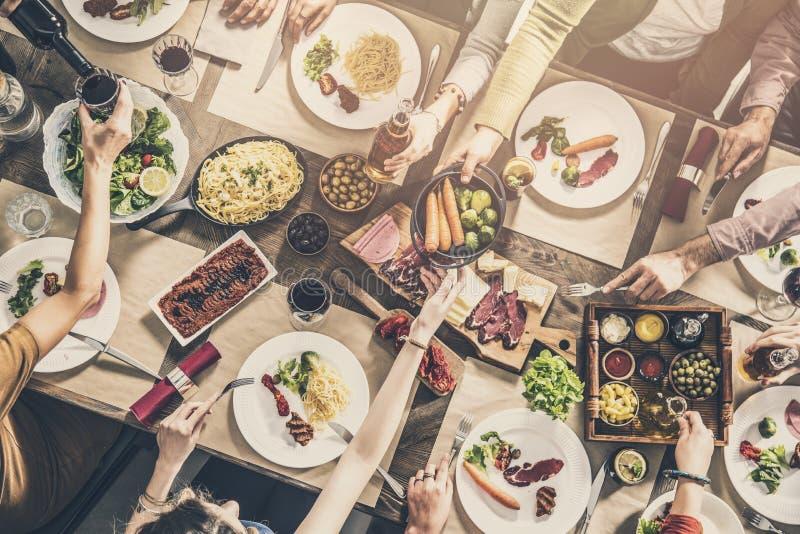 Gruppe von Personen, die das Mahlzeitzusammengehörigkeitsspeisen hat stockbild