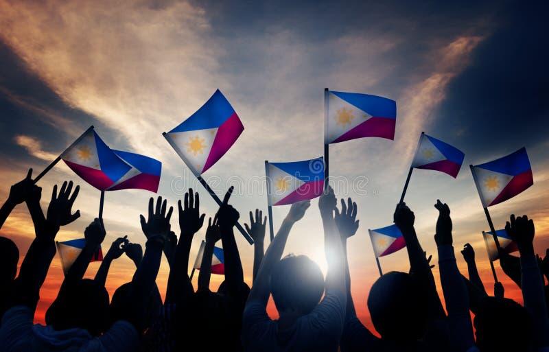 Gruppe von Personen, die philippinische Flaggen in hintergrundbeleuchtetem wellenartig bewegt lizenzfreie stockfotografie