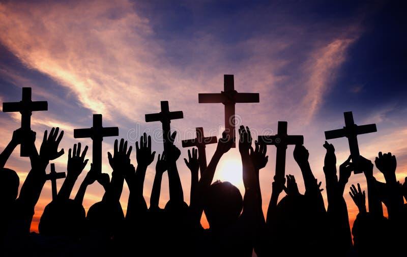 Gruppe von Personen, die Quer hält und in hintergrundbeleuchtetem betet stockbilder
