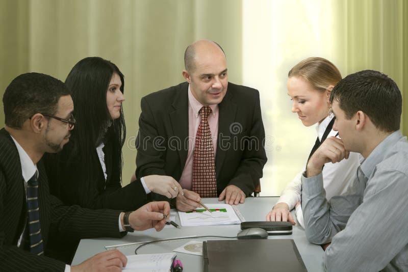 Gruppe von Personen, die am Tisch behandelt lizenzfreie stockfotos