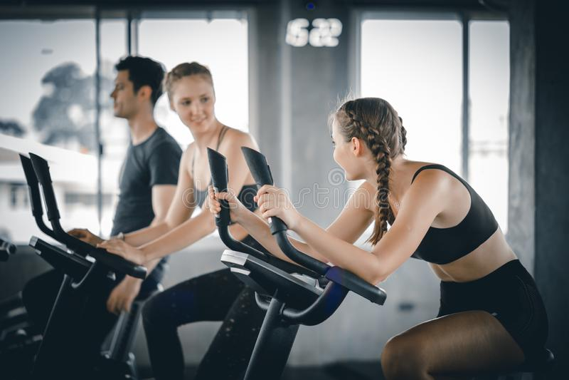 Gruppe von Personen, die in die Turnhalle, die Beine ausübend radfährt, die Radfahrenfahrräder des Herz Trainings tun lizenzfreie stockfotografie
