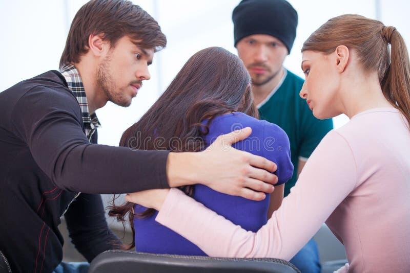 Gruppe von Personen, die umgekippte Frau tröstet. stockfoto