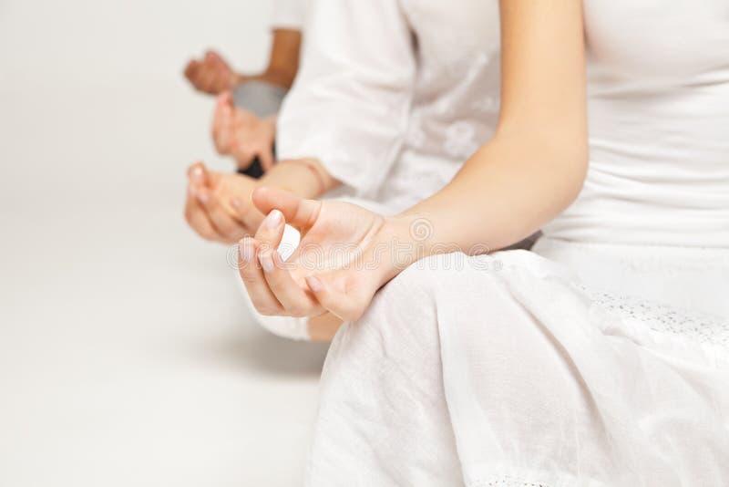 Gruppe von Personen, die Yoga im Weiß sich entspannt und tut lizenzfreie stockbilder