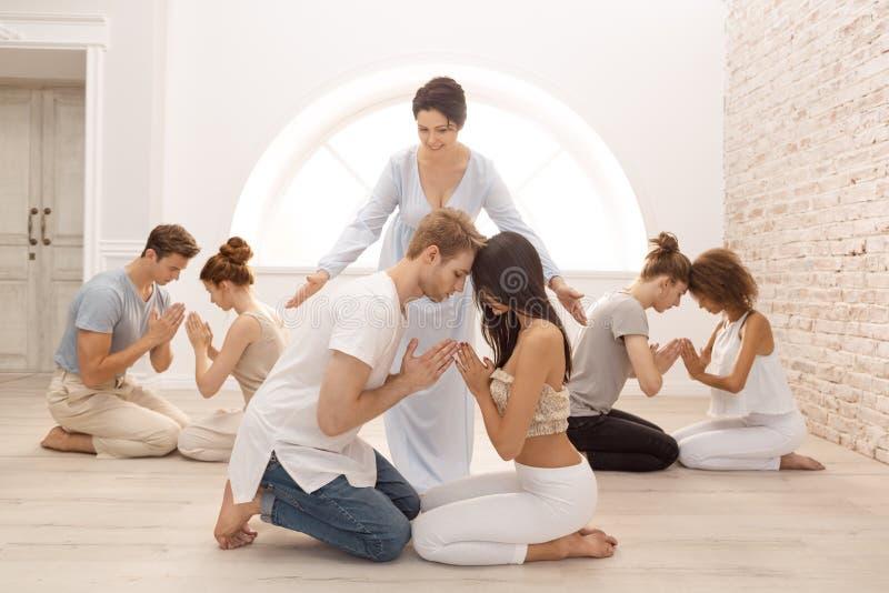 Gruppe von Personen, die zuhause meditiert Junge Familientherapie lizenzfreie stockfotos