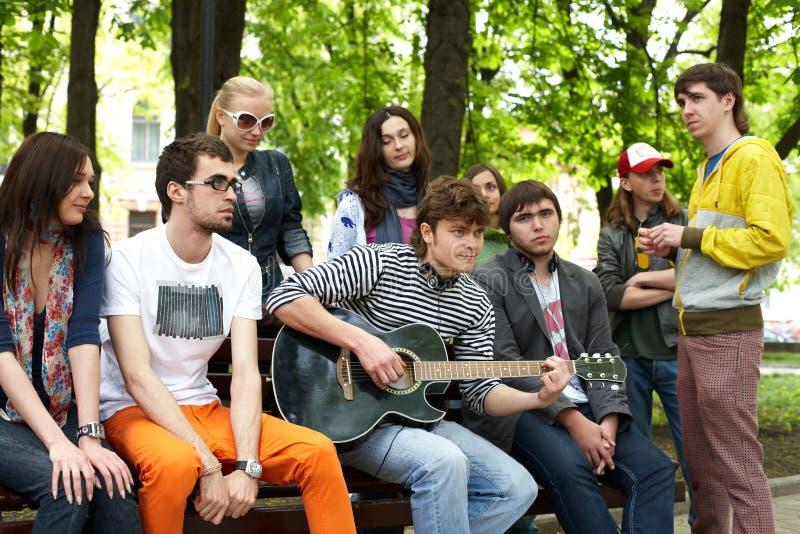 Gruppe von Personen im Stadtpark hören Musik. lizenzfreie stockfotografie