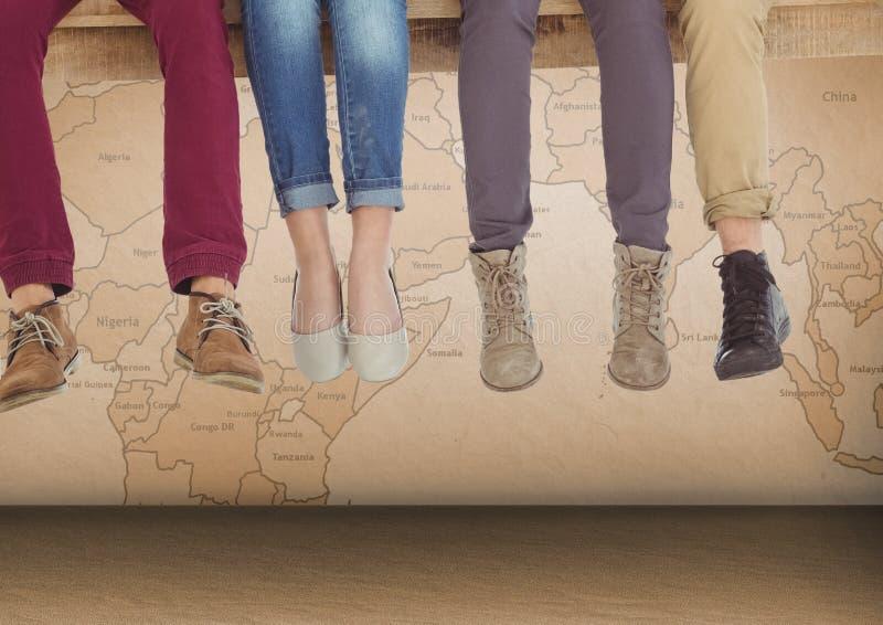 Gruppe von Personen ` s Beine, die auf hölzerner Planke vor Weltkarte sitzen lizenzfreie stockfotos