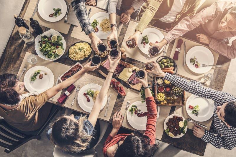 Gruppe von Personen, welche die Mahlzeitzusammengehörigkeit speist hat, Gläser röstend lizenzfreie stockfotos