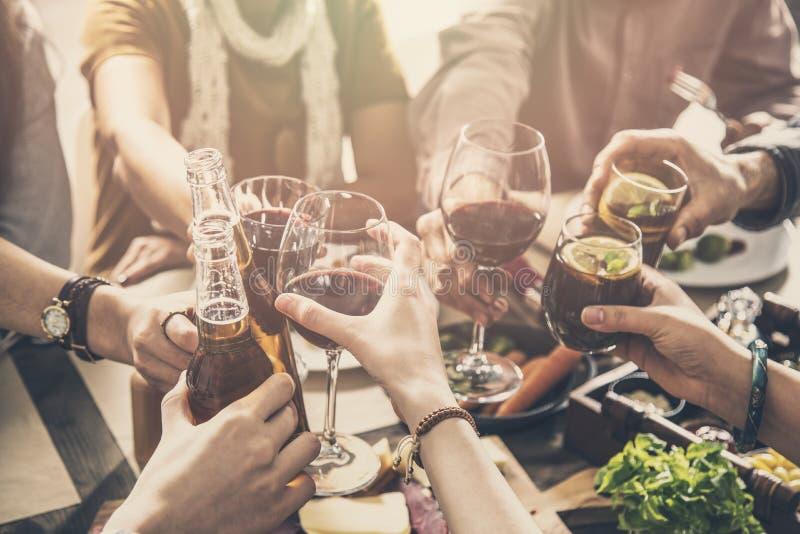 Gruppe von Personen, welche die Mahlzeitzusammengehörigkeit speist hat, Gläser röstend lizenzfreie stockfotografie