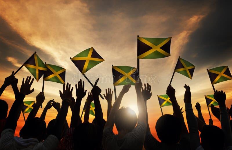 Gruppe von Personenen-wellenartig bewegende Flagge von Jamaika in hintergrundbeleuchtetem stockfotos
