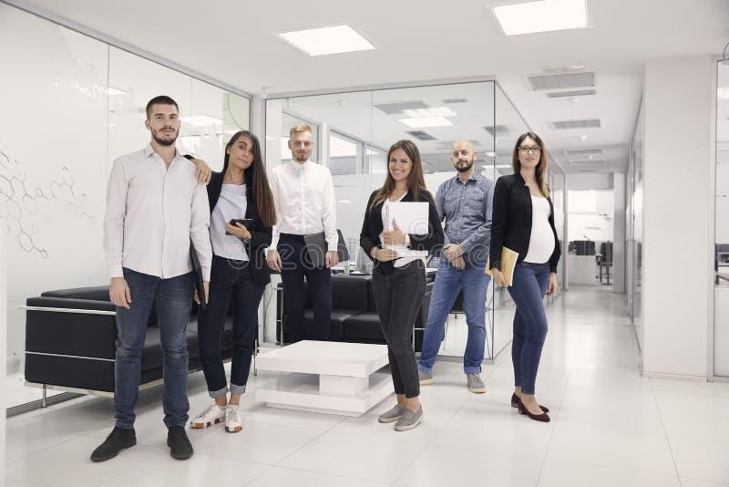 Gruppe von sechs Leuten, die, die Kamera aufwerfen, 20-29 Jahre und 30-39 Jahre betrachtend alt, von den verschiedenen Büroangest lizenzfreie stockfotografie