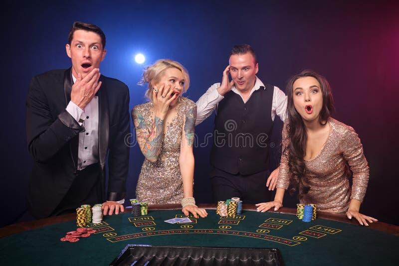 Gruppe von stilvolle reiche Freunde spielen Schürhaken am Kasino lizenzfreie stockfotos
