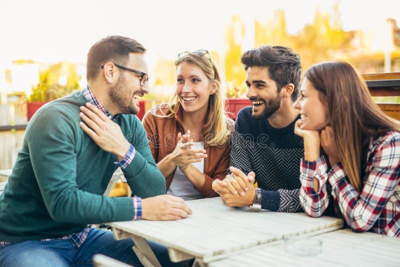 Gruppe von vier Freunden, die Spaß ein Kaffee zusammen haben stockfotografie