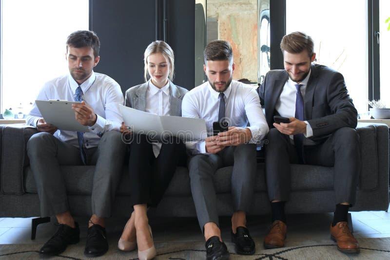 Gruppe von vier Gesch?ftsleuten, die auf Sofa sitzen Sie konnten nicht ?ber zusammenarbeiten gl?cklicher sein lizenzfreie stockbilder