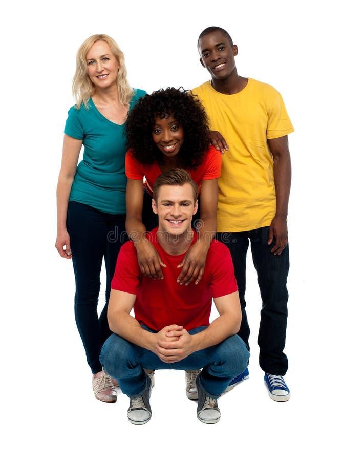 Gruppe von vier glücklichen jungen Leuten stockbild