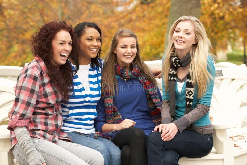 Gruppe von vier Jugendlichen, die auf Bank sitzen stockbilder