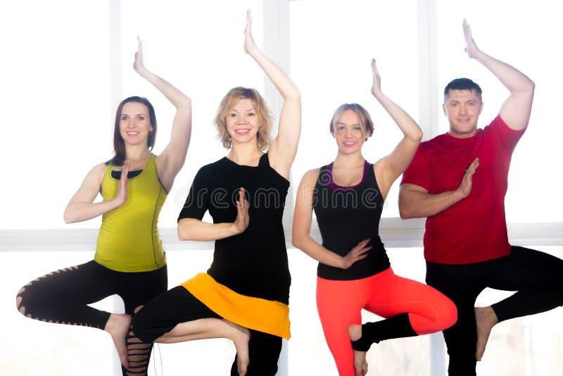 Gruppe von vier positiven Leuten, die Yoga tun, üben in der Klasse lizenzfreie stockfotografie