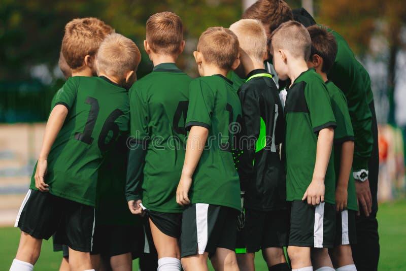 Gruppe von Young Boys in den Hemden des grünen Trikots, die mit Trainer auf Fußballplatz stehen lizenzfreies stockbild