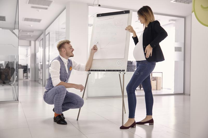 Gruppe von zwei jungen Leuten, von Geschäftsmann und von schwangerer Geschäftsfrau, Geschäftstreffen presentaion, stellend an Bor stockfoto