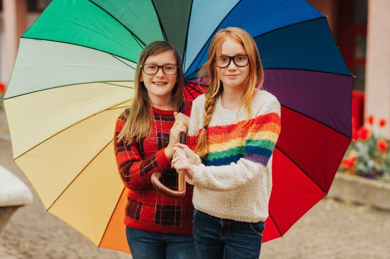 Gruppe von zwei netten kleinen Mädchen, die draußen unter großem buntem Regenschirm spielen lizenzfreies stockbild