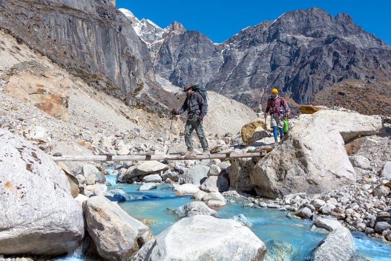 Gruppe Wanderer, die Gebirgsflusswurfsholzbrücke kreuzen lizenzfreies stockfoto