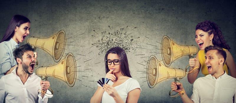Gruppe Wirtschaftler, die in den Megaphonen an einer verwirrten Frau mit mehrfachen Kreditkarten schreien stockbilder