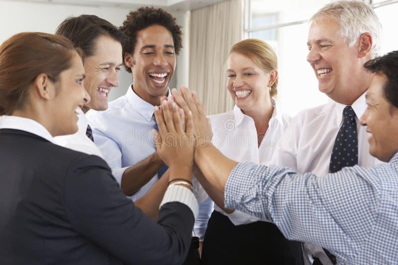 Gruppe Wirtschaftler, die Händen im Kreis auf Firmenseminar sich anschließen stockfotografie