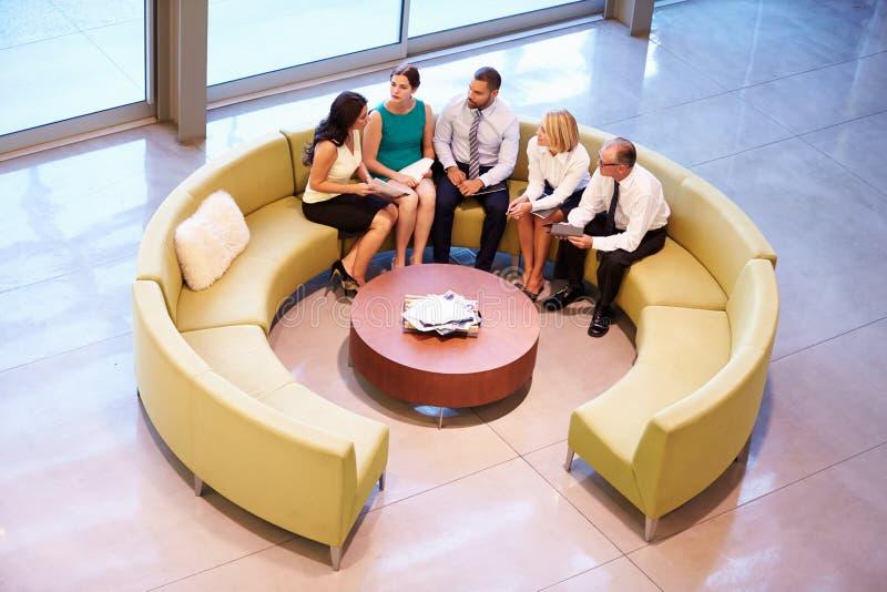Gruppe Wirtschaftler, die Sitzung in der Büro-Lobby haben lizenzfreie stockfotos