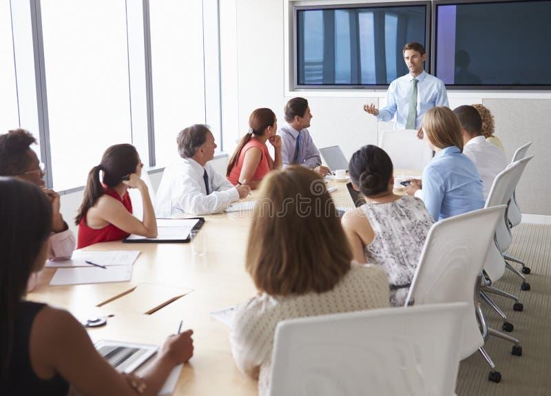 Gruppe Wirtschaftler, die um Sitzungssaal-Tabelle sich treffen lizenzfreie stockfotografie