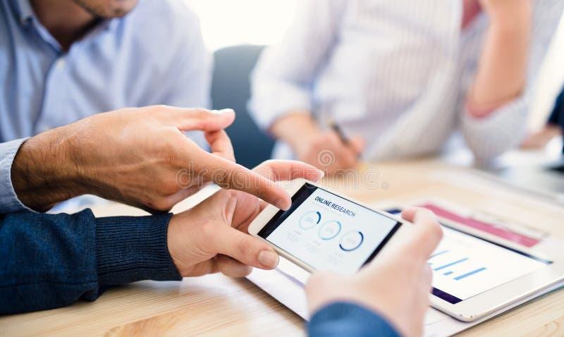 Gruppe Wirtschaftler mit Smartphonefunktion zusammen im Büro, Mittelteil stockbild