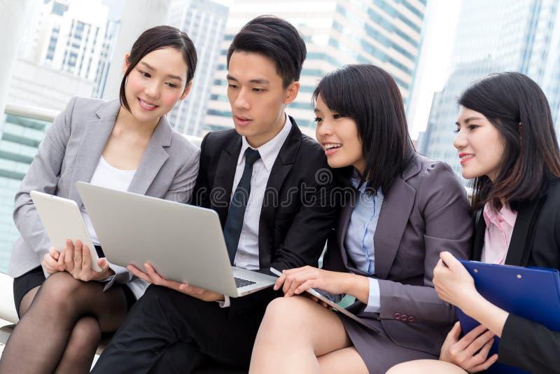 Gruppen av affären diskuterar på bärbar datordatoren royaltyfri foto
